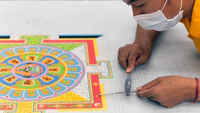 To create rich details and ornamentation, the monks layer the brightly colored sand, forming patterns.
